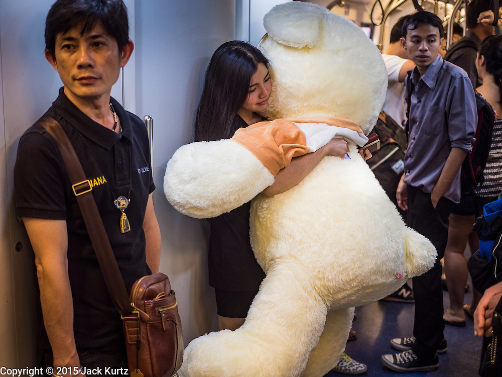 22 SEPTEMBER 2015 - BANGKOK, THAILAND:  A woman on the Sukhmvit Skytrain line with a large stuffed teddy bear.     PHOTO BY JACK KURTZ