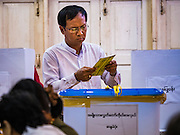 08 NOVEMBER 2015 - YANGON, MYANMAR: A man reviews his ballot before putting them in a ballot box in a polling place in central Yangon. The citizens of Myanmar went to the polls Sunday to vote in the most democratic elections since 1990. The National League for Democracy, (NLD) the party of Aung San Suu Kyi is widely expected to get the most votes in the election, but it is not certain if they will get enough votes to secure an outright victory. The polls opened at 6AM. In Yangon, some voters started lining up at 4AM and lines were reported to long in many polling stations in Myanmar's largest city.      PHOTO BY JACK KURTZ