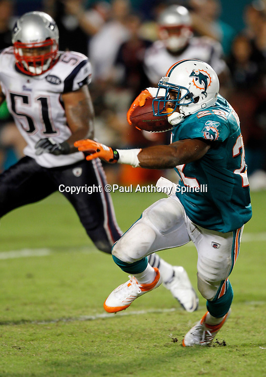 Miami Dolphins running back Reggie Bush (22) runs the ball during the NFL week 1 football game against the New England Patriots on Monday, September 12, 2011 in Miami Gardens, Florida. The Patriots won the game 38-24. ©Paul Anthony Spinelli