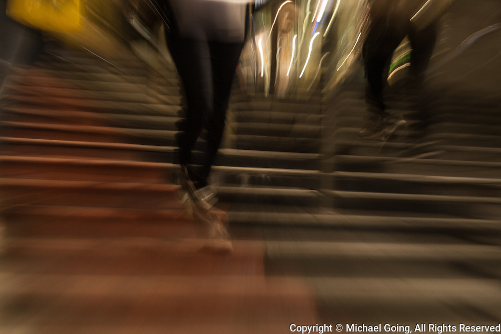 Motion blur from waist down of pedestrians descending wide outdoor stairway