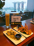 "Singapore. Level 33 Restaurant & Lounge offers ""experimental penthouse dining in the World's highest urban craft-brewery."" View towards Marina Bay Sands Hotel."