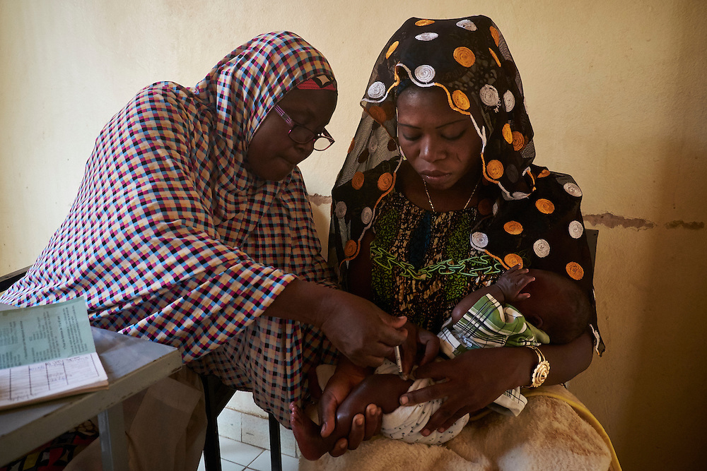 Nurse Amadou Aissatou administers vaccinations to baby Zoubeyrou, 6 weeks old held by mother Viviane Nisé  at the Banga Bana health centre, Niamey, Niger on February 16, 2016.