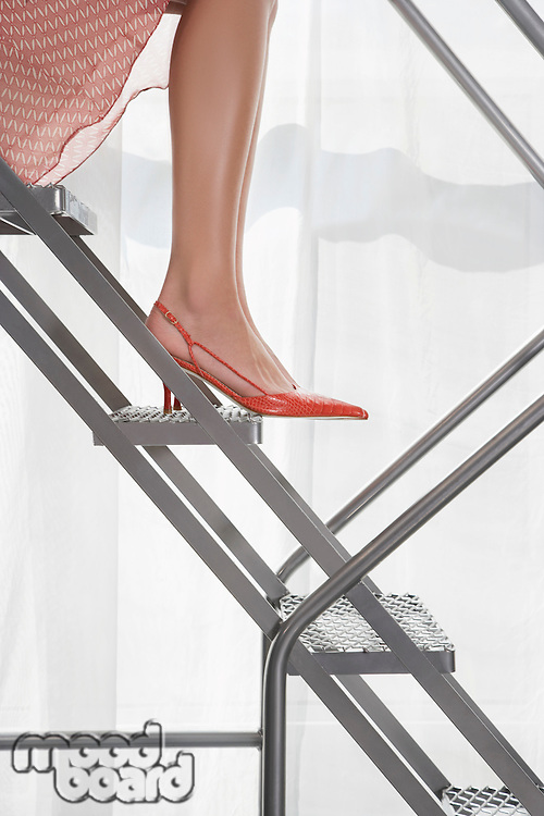 Young woman wearing high heeled shoes sitting on aluminium staircase low section side view
