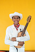 A Son Jarocho musician poses for a portrait with his traditional jarana jarocha guitar in Tlacotalpan, Veracruz, Mexico. The tiny town is painted a riot of colors and home to legendary Mexican musician Agustín Lara.