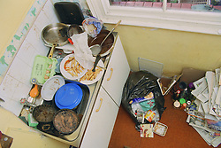 Kitchen sink in house full of dirty plates and pans; with piles of rubbish on floor,