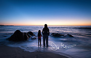 A mother and daughter hold hands and watch the sunrise over the Pacific Ocean together.