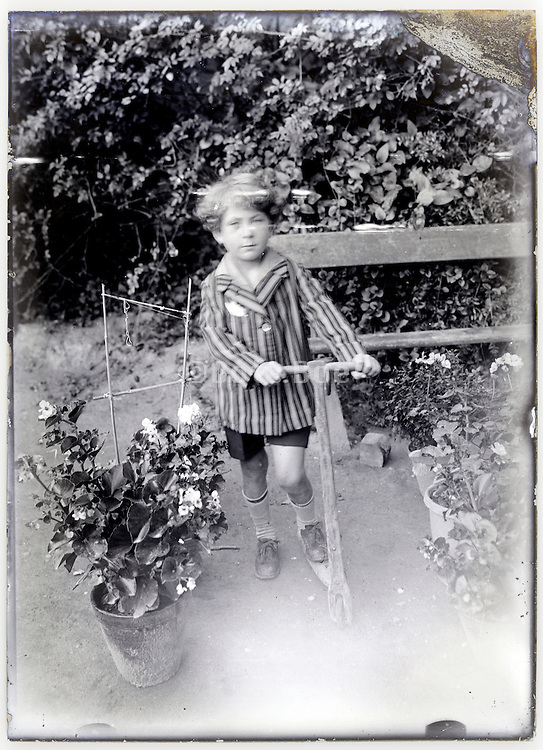 little boy with step toy scooter in garden setting on a eroding glass plate
