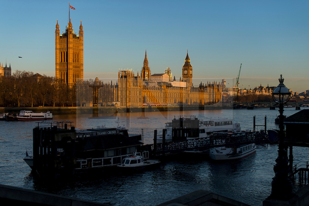 © Licensed to London News Pictures. 28/01/2016. London, UK. Warm orange sunshine cast over the Houses of Parliament in Westminster on a clear day at sunrise in London on a cold winter morning. Photo credit: Ben Cawthra/LNP