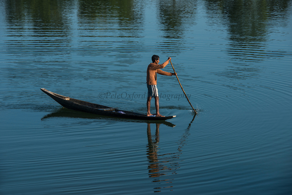 Fisherman in canoe<br /> Mising Tribe (Mishing or formally Miri Tribe)<br /> Majuli Island, Brahmaputra River<br /> Largest river island in India<br /> Assam,  ne India