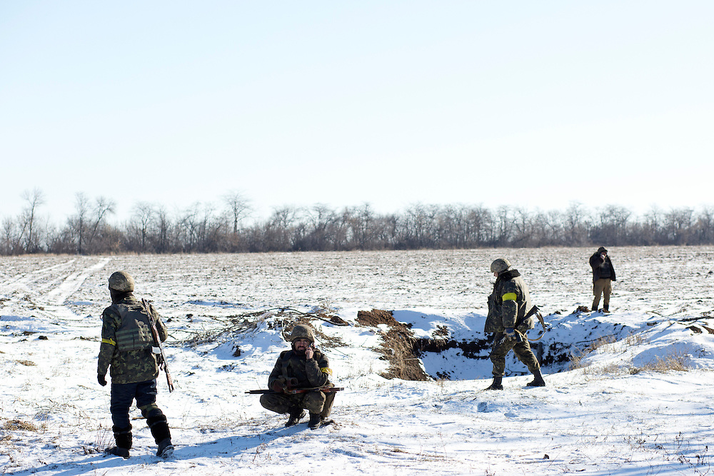 Soldiers make phone calls and rest in a field on February 18, 2015 on a road about 35 kilometers from Debaltseve, Ukraine. The soldiers had withdrawn from Debaltseve earlier in the day and were regrouping at a crossroads before heading towards Artemivsk.
