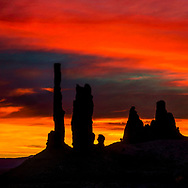 Silhouette of a rock formation from Monument Valley against fiery red sunset