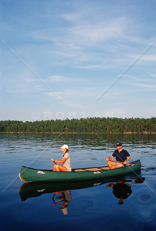 Couple outdoors in a canoe on a peaceful lake in New Hampshire