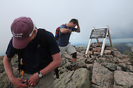 John Walcott, left, puts away his camera after taking a photograph of the sign at the summit of Mt Katahdin, the northern terminus of the Appalachian Trail and highest point in Maine, while Jared Leonard prepares to rest.  Walcott has been climbing Katahdin since 1976 and was celebrating his 60th birthday.