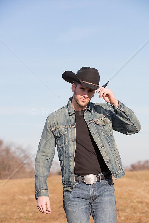 Rugged cowboy in a denim jacket on a ranch