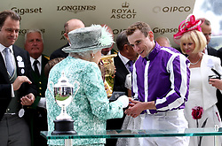Queen Elizabeth II presents a medal to jockey Ryan Moore after he rode Merchant Navy to victory in the Diamond Jubilee Stakes during day five of Royal Ascot at Ascot Racecourse.