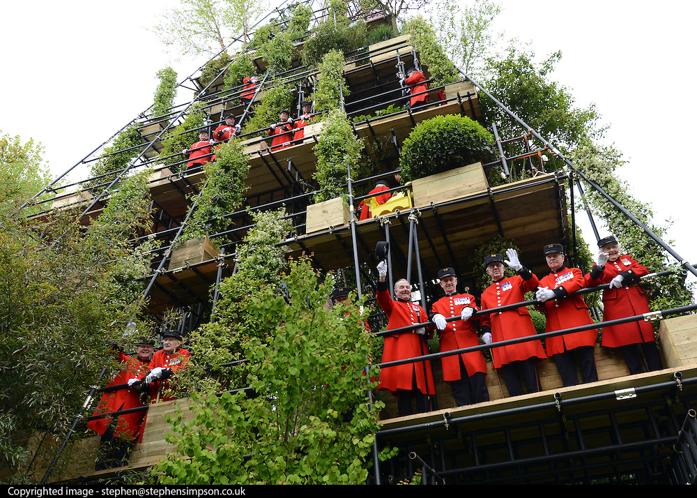 © Licensed to London News Pictures. 21/05/2012. Chelsea, UK. Chelsea Pensioners dressed in their distinctive red coats stand on Diarmuid Gavin's 24-metre tall pyramid-shaped designed garden. Press preview of The Chelsea Flower Show today 21 May 2012. The world's most famous flower show, which has been held in the grounds of the Royal Chelsea Hospital since 1913, will be open to the public from Tuesday. Visitors are expected to flock in their thousands to see displays of plants, flowers and furniture for ideas on how to decorate their gardens.. Photo credit : Stephen Simpson/LNP