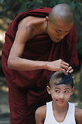 Young novice Monk having his head shaved with smirk on his face
