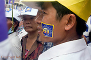 A man is listening to a speaker at an election campaign rally for opposing CNRP led by Sam Rainsy in Kampong Cham, Cambodia.