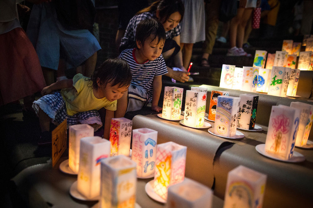 NAGASAKI, JAPAN - AUGUST 8 : Children look at candle-lit paper lanterns with written message at Nagasaki Peace Park on the eve ahead of the 71st anniversary activities, commemorating the atomic bombing of Nagasaki on August 8, 2016 in Nagasaki, southern Japan. On August 9, 1945, during World War II, the United States dropped the second Atomic bomb, a plutonium implosion-type bomb on Nagasaki city, killing an estimated 40,000 people which ended the World War II. (Photo by Richard Atrero de Guzman/NURPhoto)