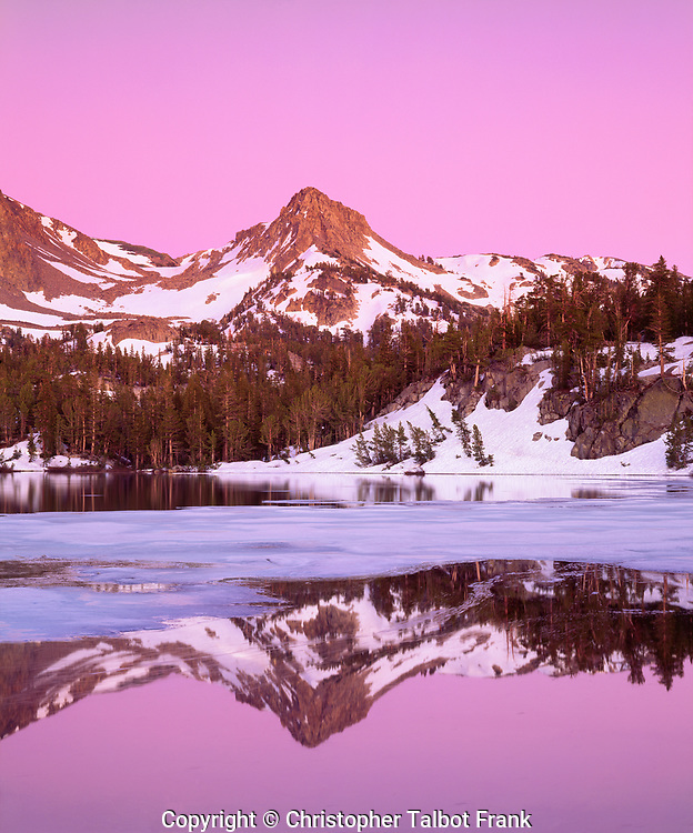 I packed my camera into the wilderness to take this photo of Skelton Lake alpine glow in the Sierra Nevada Mountains.  The incredible pink colors came as dusk colored the mountain peak that reflected in the partially frozen lake.