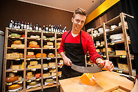 Portrait of confident male salesperson cutting cheese in store