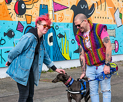 Edinburgh, Scotland, 03 May 2019. Pictured: 'Blue', an Irish Greyhound and former racing dog, who is in training as a therapy dog to help people with anxiety and depression with mural artist Katie Guthrie at the Edinburgh Dog & Cat Home mural unveiling. , The 80 foot mural is unveiled today as a colourful addition to Seafield promenade. It is designed and painted by local artists Studio N_Name. It depicts the people, heritage and environment of the local community and features flora, fauna and historic elements of the local coastline. It has been made possible through through partnership with Edinburgh Shoreline Project. It is on the seafront wall of the dog & cat home which rescues, reunites and rehomes lost, stray and abandoned dogs and cats across Edinburgh and the Lothians, caring for 2,367 dogs and 771 cats in 2018.<br /> Sally Anderson | EdinburghElitemedia.co.uk