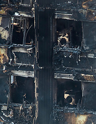 © Licensed to London News Pictures. 15/06/2017. London, UK. What appear to be a washing machines. The burnt out remains of the inside of some of the apartments can be seen the Grenfell tower block in west London. The blaze engulfed the 27-storey building with hundreds of firefighters attending the scene. Photo credit: Ben Cawthra/LNP