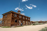 Two visitors look in a window of the Bodie Schoolhouse, one of the largest remaining structures at the California ghost town and National Historic Landmark.