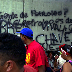 """In Venezuela's pro-Chavez neighborhoods of western Caracas pedestrians crowd a business district where pro-chavez grafitti reads """"People of Petrol. Long live the people!"""""""