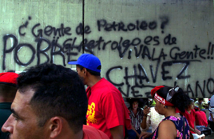 "In Venezuela's pro-Chavez neighborhoods of western Caracas pedestrians crowd a business district where pro-chavez grafitti reads ""People of Petrol. Long live the people!"""