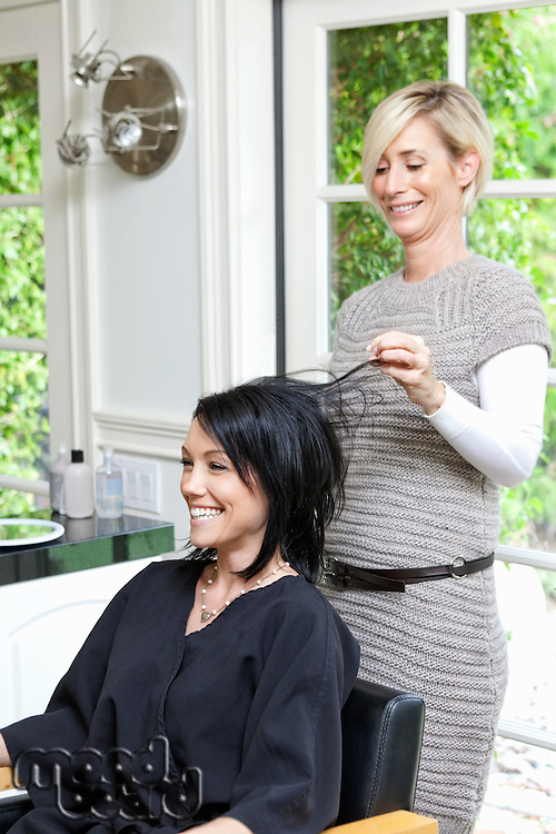 Cheerful hairstylist looking at hair of beautiful woman in beauty salon