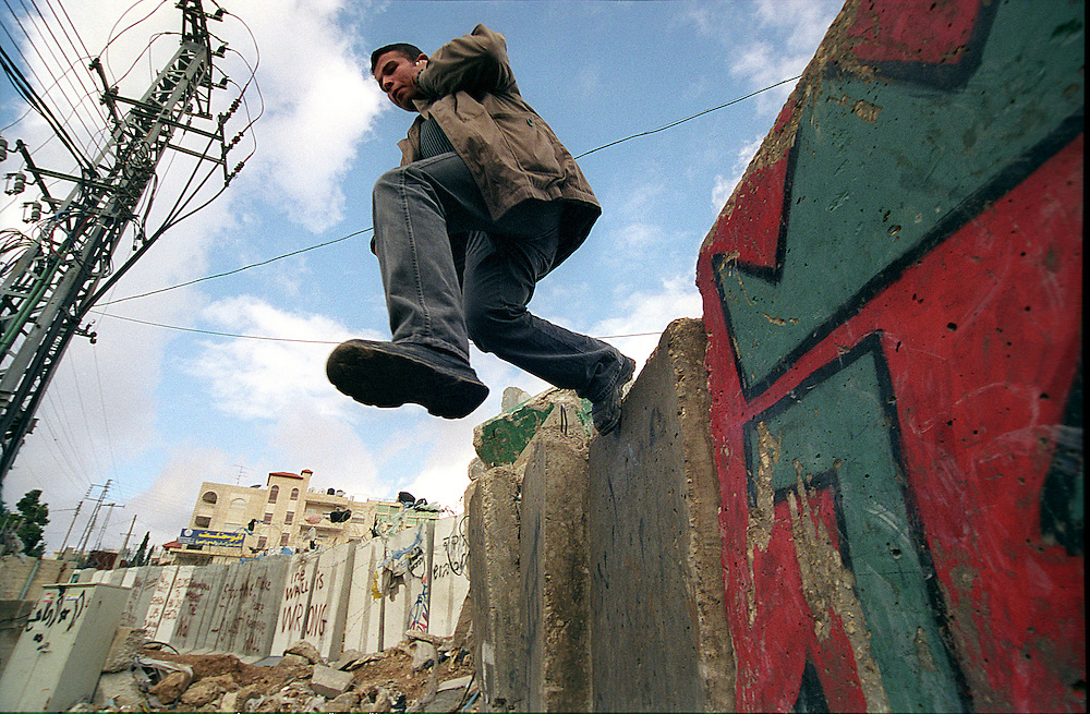 A  Palestinian man jumps over the separation wall at the West Bank village of Abu Dis on Monday, 10 July ,2005. Israel government decided Sunday on a new route for the separation fence surrounding the Jerusalem area, which will result in some 55,000 Palestinian residents of East Jerusalem being cut off from the rest of the city. PHOTO BY Olivier Fitoussi