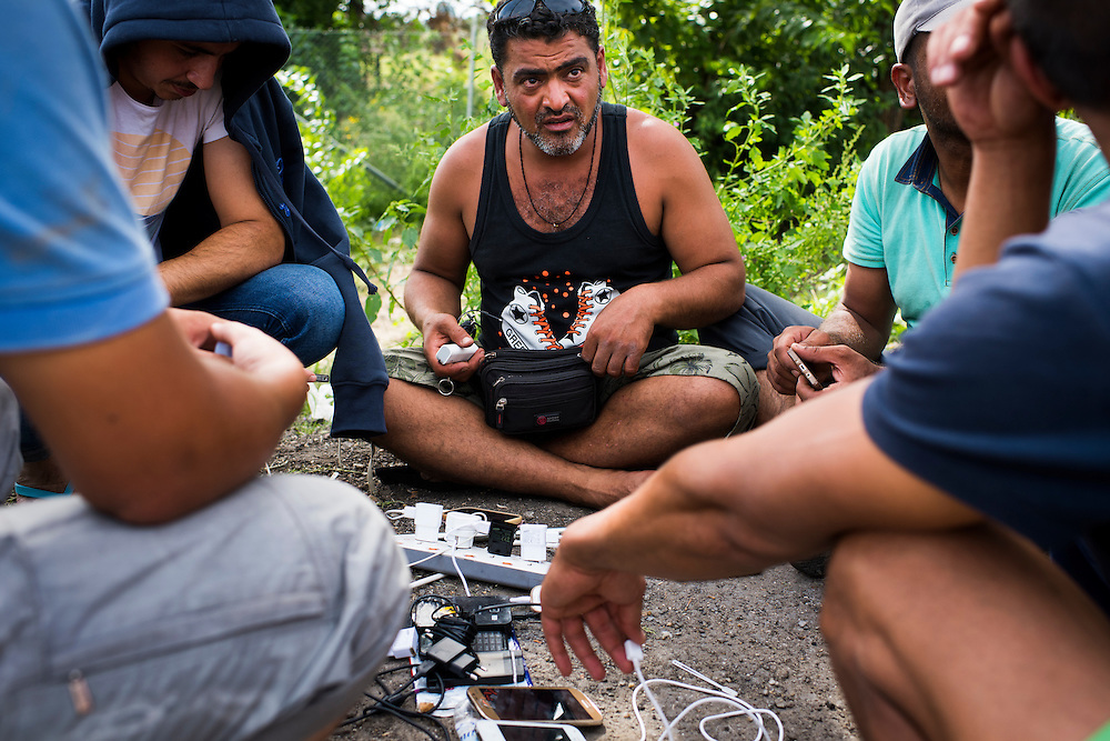 Migrants converse while using a generator to charge their phones on September 17, 2015 in Horgos, Serbia.