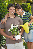 Portrait of couple in garden with gardening tools