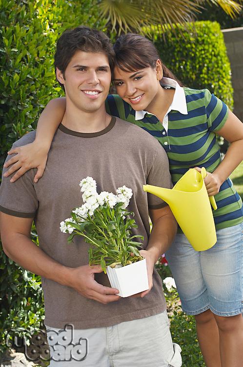 Portrait of couple in garden with gardening tools