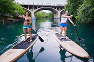 Two women stand up paddle boarding near Barton Springs in Austin, Texas.