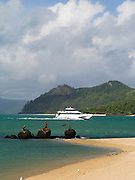 A Whitsunday Island Cruise boat passes by the Three Mermaids statues on Daydream Island; Whitsunday Islands, QLD, Australia