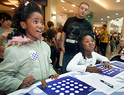 "Cadburys Spots vs Stripes Challenge Race Season Meadowhall Sheffield.Berddine and Deborah Kuskisa take part in the ""fastest coin stacker"".2 April 2011.Images © Paul David Drabble"