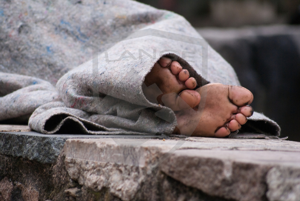 the feet of a homeless carioca stick out from underneath a blanket in centro, rio de janeiro, brazil.  the disparity in wealth distribution within the city of rio de janeiro is jarring as the government continues to implement legislation to curb the polarized socioeconomic climate.