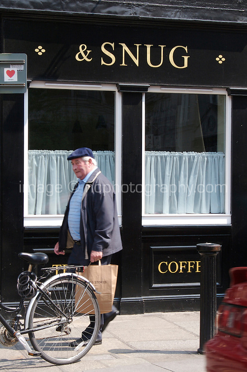 Senior man carrying paper shopping bag past a bar in Dublin Ireland