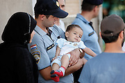 Croatian policeman holds a baby from Syria during the migrants registration process in Tovarnik.