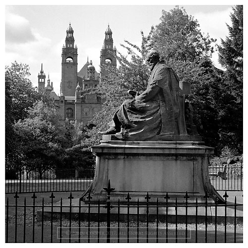 Black and white photograph of the statue of Lord Kelvin on Kelvin Way and Kelvingrove Art Gallery & Museum in Glasgow. Mounted print available to purchase.