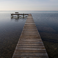 Cayman Islands, Little Cayman Island, Morning sun lights boat pier along Caribbean Sea