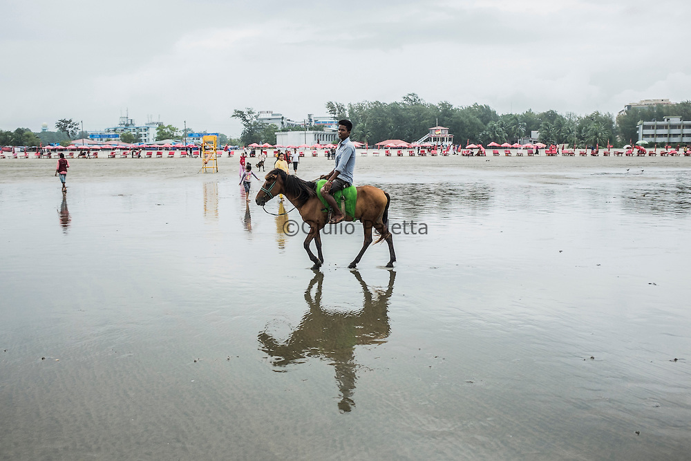 A young boy wait for tourists to carry on his horse, on the beach of Cox's Bazar, Bangladesh