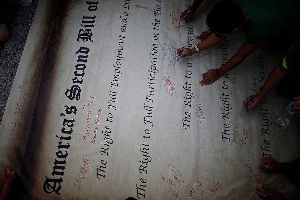 Protesters participating in a Florida American Federation of Labor and Congress of Industrial Organizations (AFL-CIO) rally sign a large copy of American's Second Bill of Rights during the 2012 Republican National Convention on August 29, 2012 in Tampa, Fla.