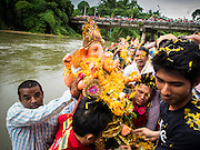 31 AUGUST 2014 - SARIKA, NAKHON NAYOK, THAILAND: A statue of Ganesh is carried along the riverbank before being submerged during the Ganesh Festival at Shri Utthayan Ganesha Temple. Ganesh Chaturthi, also known as Vinayaka Chaturthi, is a Hindu festival dedicated to Lord Ganesh. It is a 10-day festival marking the birthday of Ganesh, who is widely worshiped for his auspicious beginnings. Ganesh is the patron of arts and sciences, the deity of intellect and wisdom -- identified by his elephant head. The holiday is celebrated for 10 days, in 2014, most Hindu temples will submerge their Ganesh shrines and deities on September 7. Wat Utthaya Ganesh in Nakhon Nayok province, is a Buddhist temple that venerates Ganesh, who is popular with Thai Buddhists. The temple draws both Buddhists and Hindus and celebrates the Ganesh holiday a week ahead of most other places.    PHOTO BY JACK KURTZ