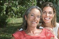 Portrait of mother with adult daughter in garden smiling close-up