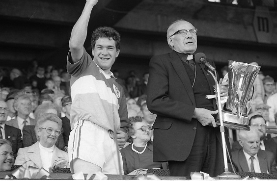 All Ireland Hurling Finals.1986..07.09.1986..09.07.1986..7th September 1986..September,every year,is the highlight of the GAA calendar with The All Ireland Finals being held in both codes. The senior and minor finals in each code are both played for on the same day. Each finalist has battled through provinical and knock out stages to reach the final.It is widely regarded as the pinnacle of a players career to reach and win an All Ireland Championship..In this years hurling finals,Cork played Offaly in the minor championship and a much fancied Galway team took on Cork in the senior final. Both matches were well fought and close encounters...In the minor final Offaly ran out winners against Cork with a score of 3.12 (21) to 3.9 (18)..Pictured here is the victorious Offaly captain, Michael Hogan,about to receive the Irish Press Cup from Dr T Morris,Archbishop of Cashel. Dr Morris is the patron of the GAA.