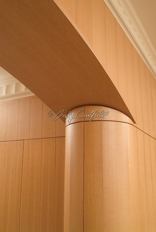Detail of craftsmanship in wooden pillar and arch in kitchen entryway built by Elias Studios.