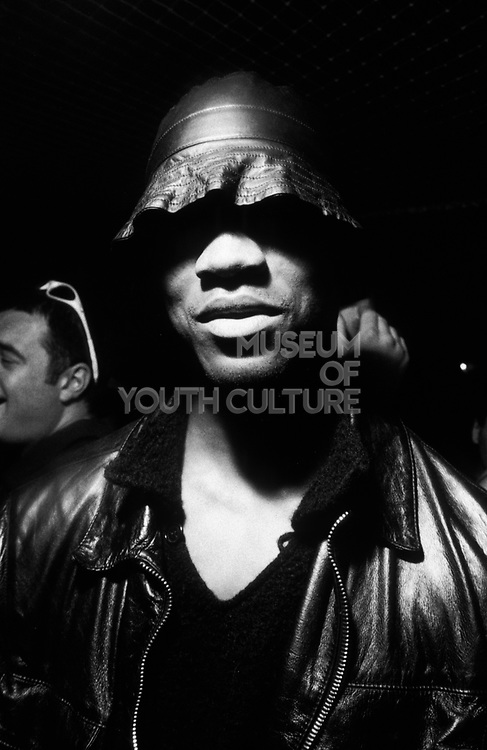Mysterious black man wearing dark leather jacket and black leather fishing hat, Queen Club / Le Batoter, Paris, France, 1999.